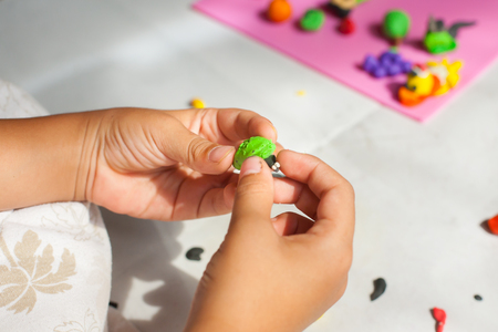 sculp: Child hands with plasticine in home at Thailand. Stock Photo