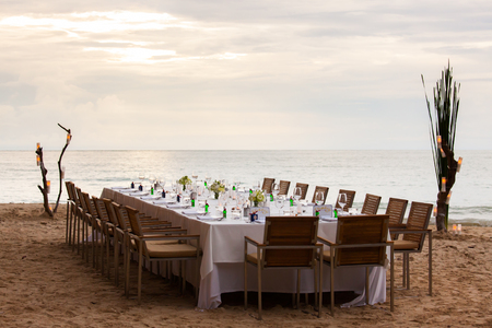 formal dinner party: Long table wedding dinner setup on the beach at  Thailand
