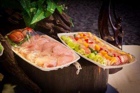 Dekoration und rohe Lebensmittel, die mit Plastikfolie verpackt für die Hochzeits-Dinner-Party vorbereitet sind.