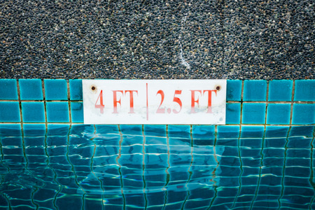 no swimming sign: pool depth sign at the edge of the swimming pool Stock Photo