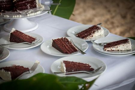 Die Hochzeitstorte wird in Stücke geschnitten. Standard-Bild