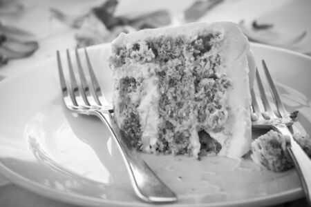 a slice of a wedding cake on dish.(Black and white)