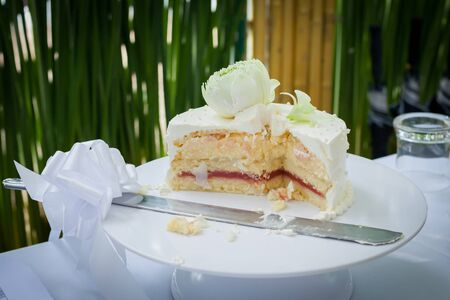 The wedding cake is cut into pieces.