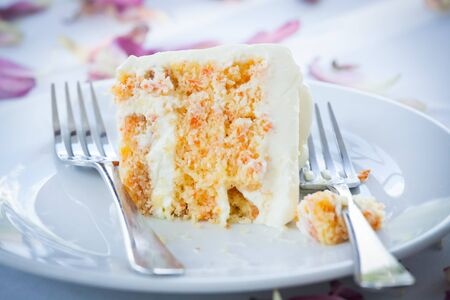 a slice of a wedding cake on dish. Imagens