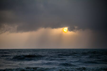 Rain storms are happening at sea at sunset time