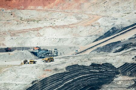 Mining dump trucks working in coalmine , Used as a source of electricity generation in the country. Banco de Imagens