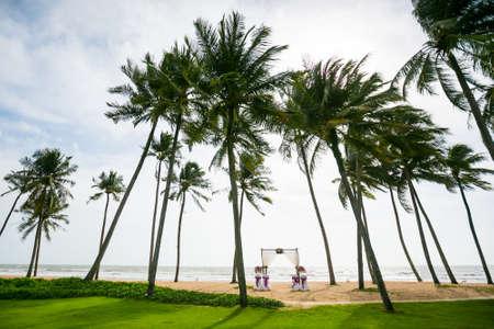wedding arch decorated on tropical sand beach, outdoor beach wedding setup. Standard-Bild