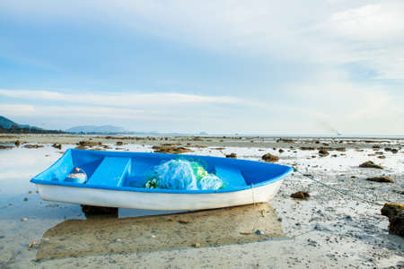 Small Fishing Boat on Sand Beach Background Banco de Imagens