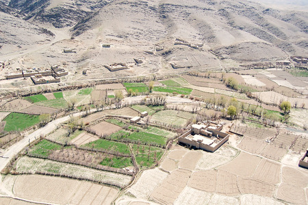 Aerial photo of a small village between Kabul and Ghazni in Afghanistan with green agricultural fields near a hillside 免版税图像 - 97530738