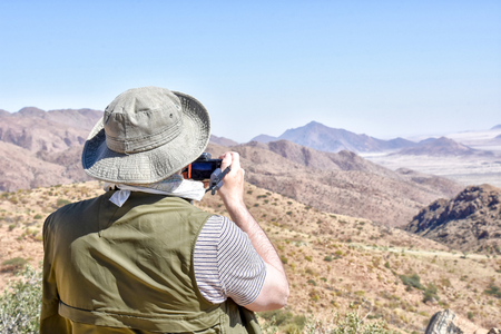 A make tourist in safari clothing and a hat overlooking and taking a photo of the valley from the top of the Spreedshoogte Pass in Namibia Southern Africa 免版税图像 - 97530747