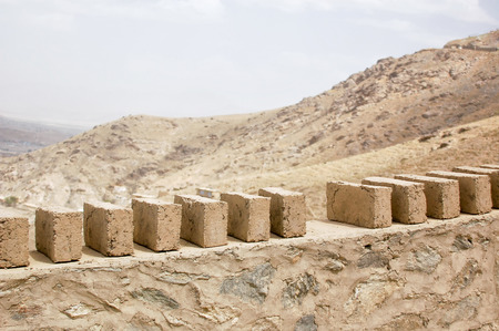 Mud bricks used for building a wall on the hillside of Kabul Afghanistan 免版税图像 - 97530748