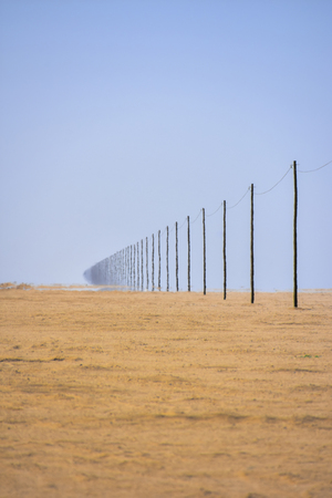 A long line of wooden poles and an electricy or telecom cable in Namibia Southern Africa near a desert road 免版税图像 - 97530749