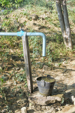 A basket made of old tires full with water under a water pipe in Myanmar Burma with vegetation in the background portraying poverty and rudimentary services