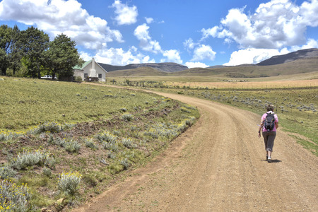In Rhodes in South Africa in the Eastern Cape with mountains and blue sky in the background and female hiker on gravel road 免版税图像
