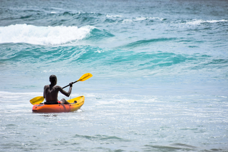 A lifeguard in a red and yellow kayak on patrol peddling on a sunny day in Coffee Bay at the Eastern Cape on the Wild Coast of South Africa 免版税图像 - 97530796