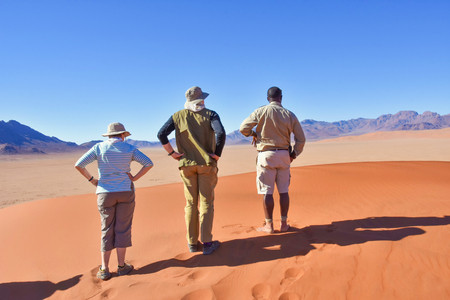 Tourists and a park ranger overlooking the valley from a sand dune in the sossusvlei desert in Namibia Southern Africa against a blue sky and majestic views 免版税图像 - 97530801
