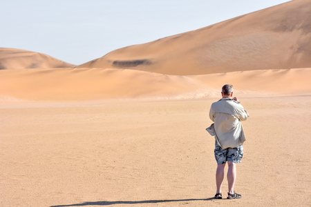 A tourist standing in the sand dunes near the coastal towns of Swakopmund and Walvisbay at the Atlantic Ocean in Namibia Southern Africa taking a photo