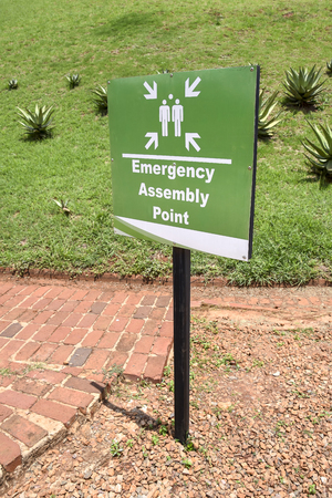 Green emergency assembly point sign commongly used in South Africa against a field with aloe plants and grass