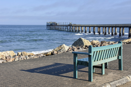 A colorful blue bench near the beach of Swakopmund Namibia Southern Africa in the early morning sun at the Atlantic Ocean against a blue sky and a jetty