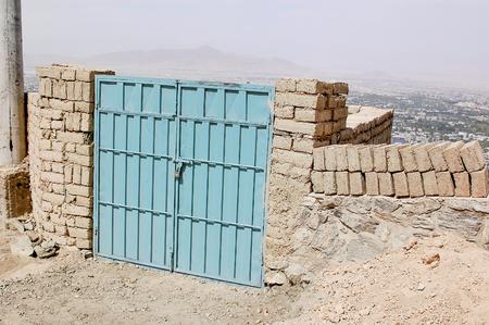 Gate to an informal settlement on the hillsides of Kabul Afghanistan 免版税图像