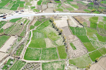 Aerial photo taken between Kabul and Ghazni in Afghanistan green agricultural fields and an asphalt road 免版税图像