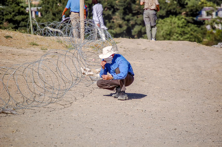 A foreigner sitting near barbed wire in Kabul Afghanistan covering his face with a cloth