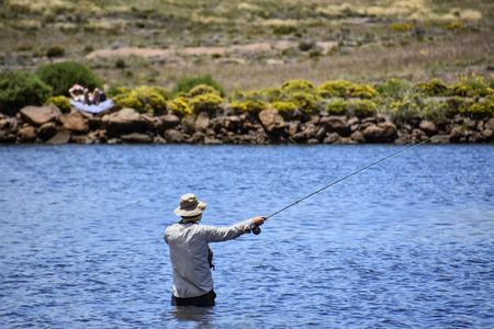 A fly fisher in the Loch Ness pond near Tiffendell near Rhodes in South Africa in the Eastern Cape with sun bather in the background 免版税图像 - 97530777