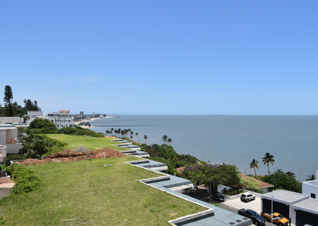 A view of the beach line of Maputo the capital of Mozambique near the Indian Ocean on a bright day with a blue sky and no clouds Stock Photo