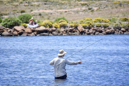 A fly fisher in the Loch Ness pond near Tiffendell near Rhodes in South Africa in the Eastern Cape with sun bather in the background 免版税图像 - 97530782