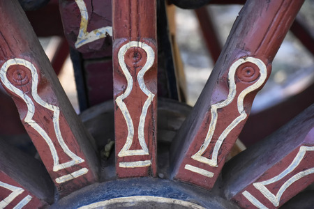 Close up of a red colored hand painted ox wagon wheel with white lines from South Africa