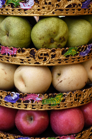Traditional Balinese offering consisting of green yellow and red apples in a stack