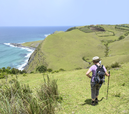 A female hiker with a hiking pole with a view of the shoreline on the trail from Coffee Bay at the Indian Ocean in the Eastern Cape at the Wild Coast of South Africa to the hole in the wall