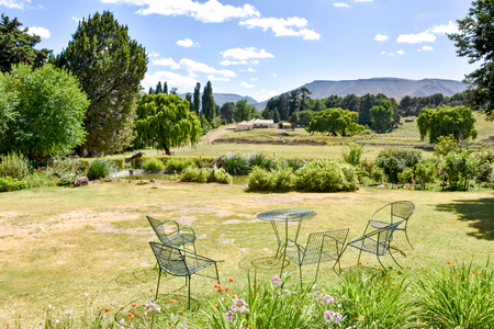 Trees, a garden furniture set and views in Rhodes in South Africa in the Eastern Cape with mountains and blue sky in the background 免版税图像 - 97530713