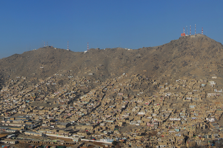Aerial photo of an informal settlement on the hillside of Kabul in Afghanistan with transmission towers on top of the mountain in a distance