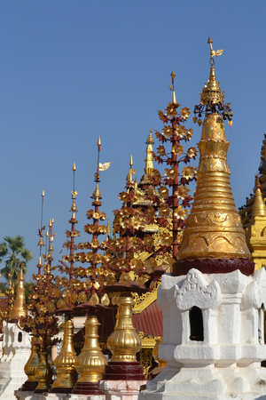 Contrasting details of a temple in Burma Myanmar with golden ornaments rising into a blue sky on a bright sunny day 免版税图像 - 96488509