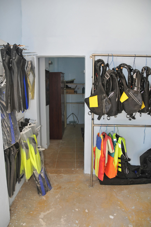 Diving gear hanging on racks including flippers, buoyancy compensation devices, and regulators 免版税图像 - 96488526