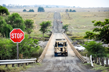 A safari vehicle moving on a bridge towards the horizon with a contrasting bright red stop sign on a black dirt road near the Isandlwana