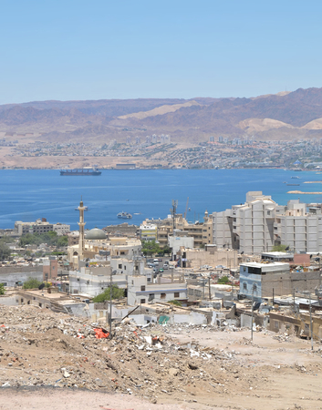 A view of Aqaba Jordan with the red sea and hills of Eilat in Israel and a blue sky in a dry desert