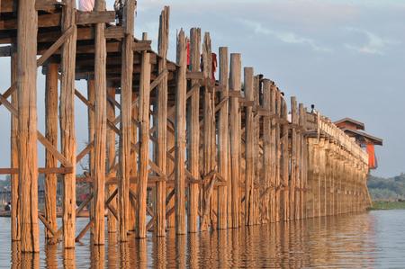 De teak U Bein-brug in Amarapura Myanmar tijdens zonsondergang met monniken en fietsen op de brug Stockfoto