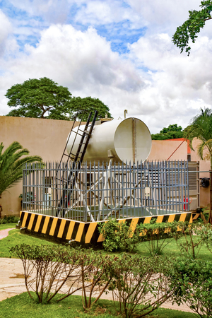 A diesel tank for a generator in Zambia with a fence and safety features with yellow and black warning signs