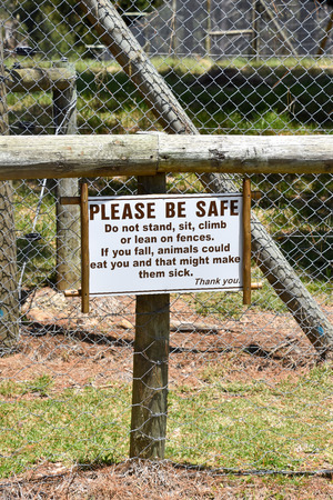 A sign saying please be safe and do not stand sit climb or lean on fences, if you fall animals could eat you and that might make them sick 写真素材