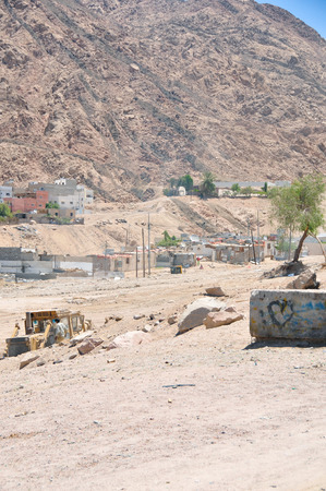 An informal settlement demolished in Aqaba in Jordan with modern houses in the background in the Middle East in a dry desert