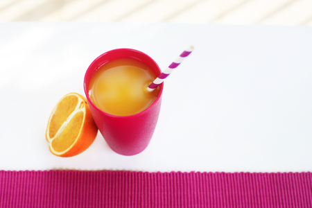 Colorful magenta glass with orange juice on a white table outside in a summer day. Served with sliced orange and two-color straw. Natural light.