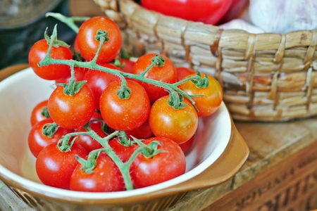 Fresh, raw vegetables for cooking:red and juicy vine-ripened cherry tomatoes in a ramekin. Selective focus. Stock Photo