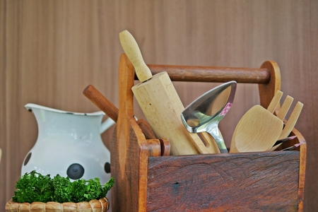 Variation of rural and vintage cooking and kitchen utensils in a wooden storage box on a table with an enameled jar and decorative plant on a wooden wall.