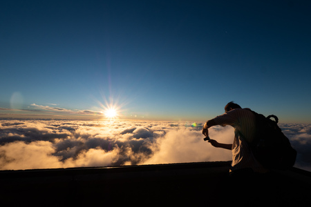 A guy is taking a photo of Beautiful dramatic sunset at Table Mountain National Park in South Africa, previously known as the Cape Peninsula National Park. Landscape with sunlight shining through gold 写真素材