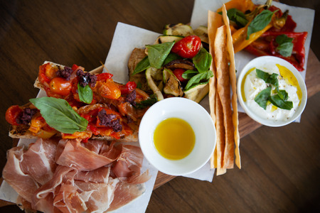 Assortment of delicious Italian antipasto:Prosciutto di Parma or Parma ham, Bruschetta topped with grilled cherry tomatoes together with grilled vegetable on a wooden board. Top View. Natural light. Stock Photo