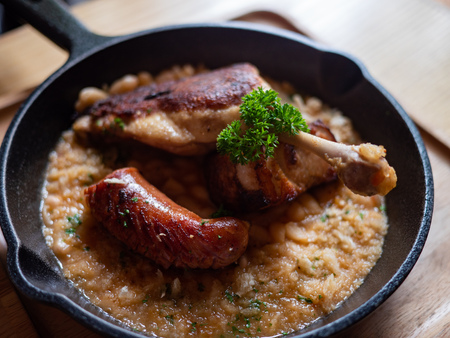 Sizzling hot, rich, slow-cooked Trio Cassoulet of duck confit, pork belly and smoked sausage on a bed of white beans in a black cast iron pan on a wooden table. Natural Light.