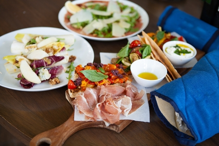 Assortment of delicious Italian antipasto:Prosciutto di Parma or Parma ham, Bruschetta and grilled vegetable on a wooden board together with kitchen mitt and foods in background. Natural light.