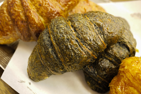 Delicious and buttery Charcoal Croissants made by pastry chef. All look very tasty and delightful. Natural light. Close up.